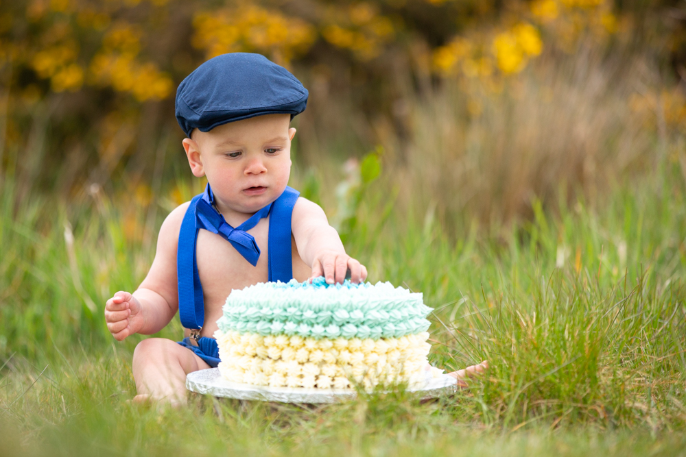 baby sees cake for the first time during his outdoor cake smash