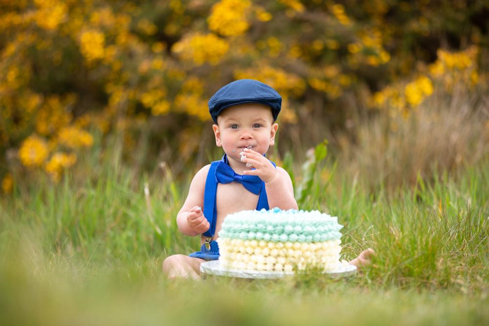baby boy enjoys his cake during cake smash outside