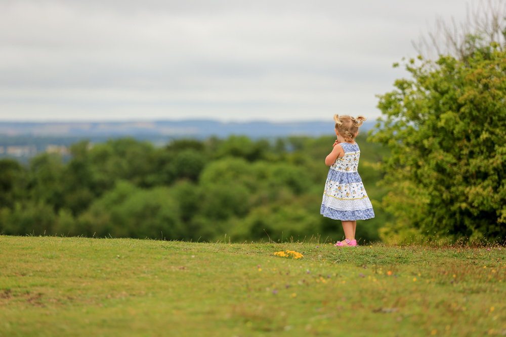 girl looks out over the horizon during a family photoshoot in Hampshire