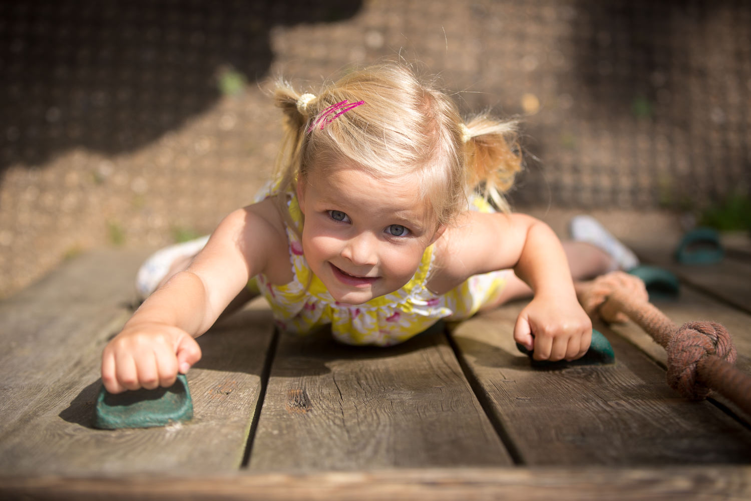 girl climbs up the climbing wall during Hilliers photoshoot
