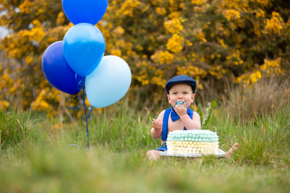 hampshiure baby photographer captures the moment a baby enjoys his first birthday cake during a cake smash in Chandlers Ford