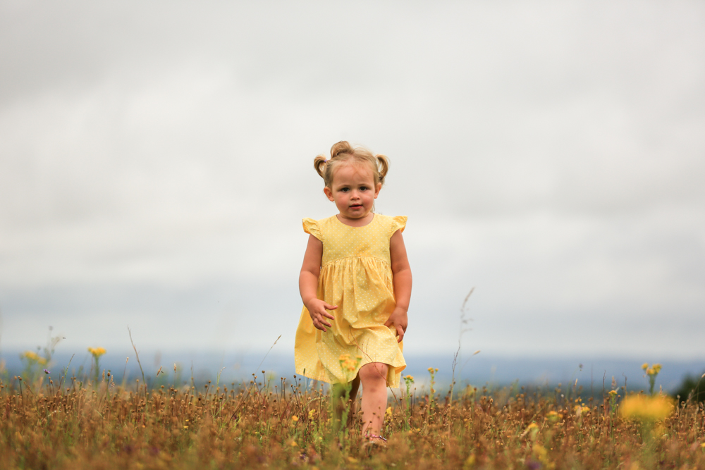 girl walks through wild grass during a family photoshoot in hampshire