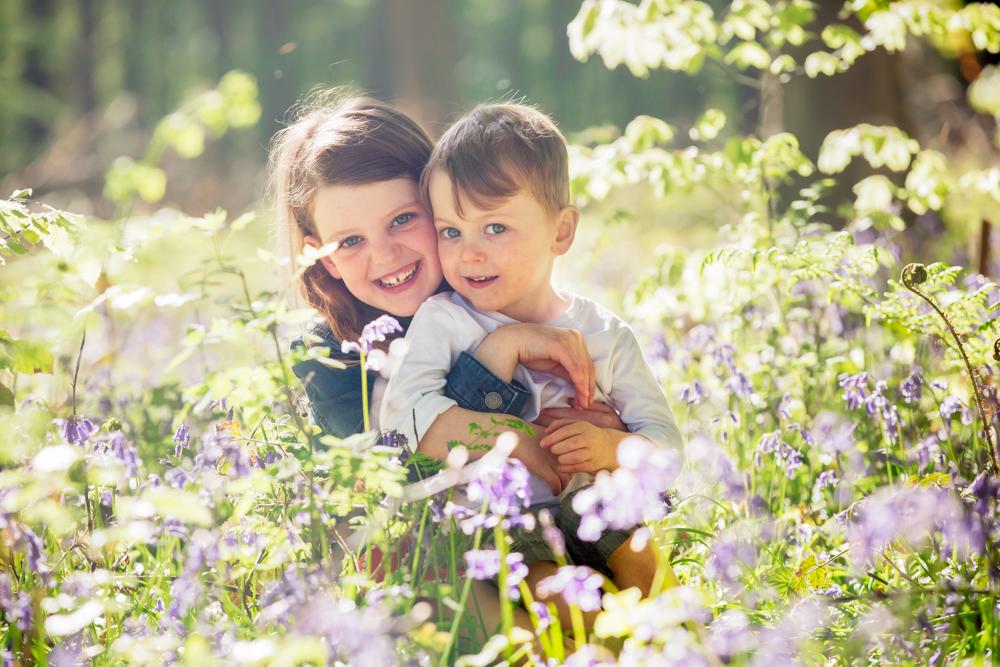 siblings cuddling in the bluebells