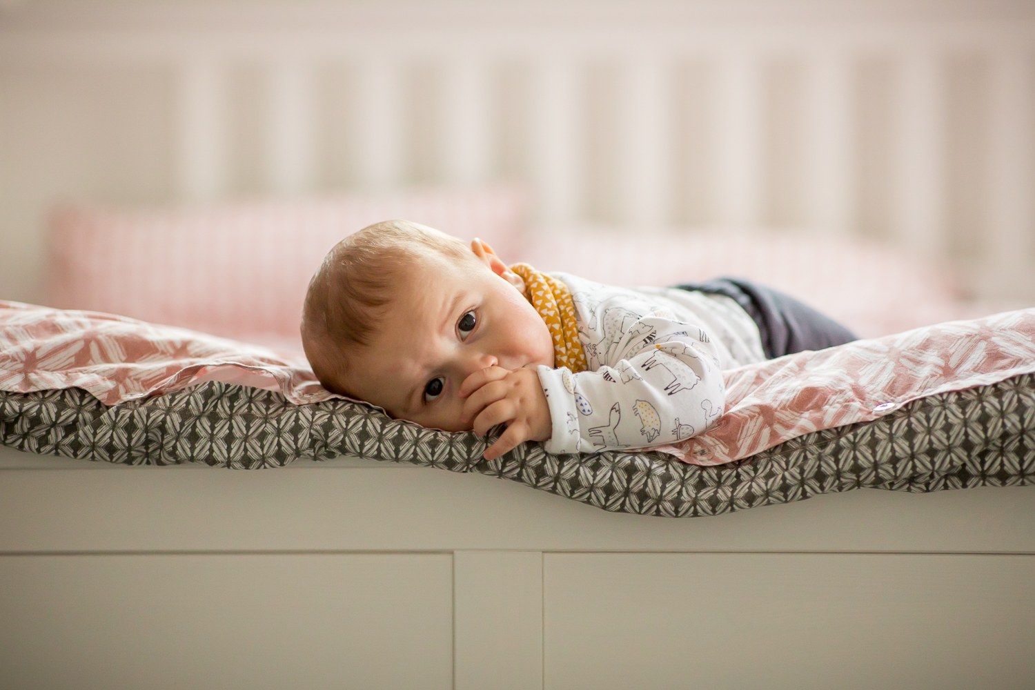 baby lying at the end of his parents bed sucking his thumb during a baby photoshoot in chandlers ford