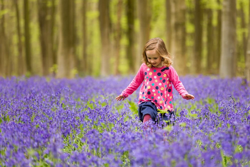 girl walking through the bluebells in bluebell photoshoot in hampshire