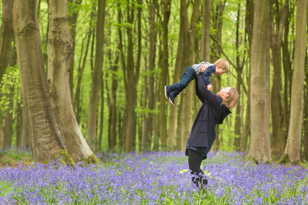 mother throws son in the air during a bluebell photoshoot