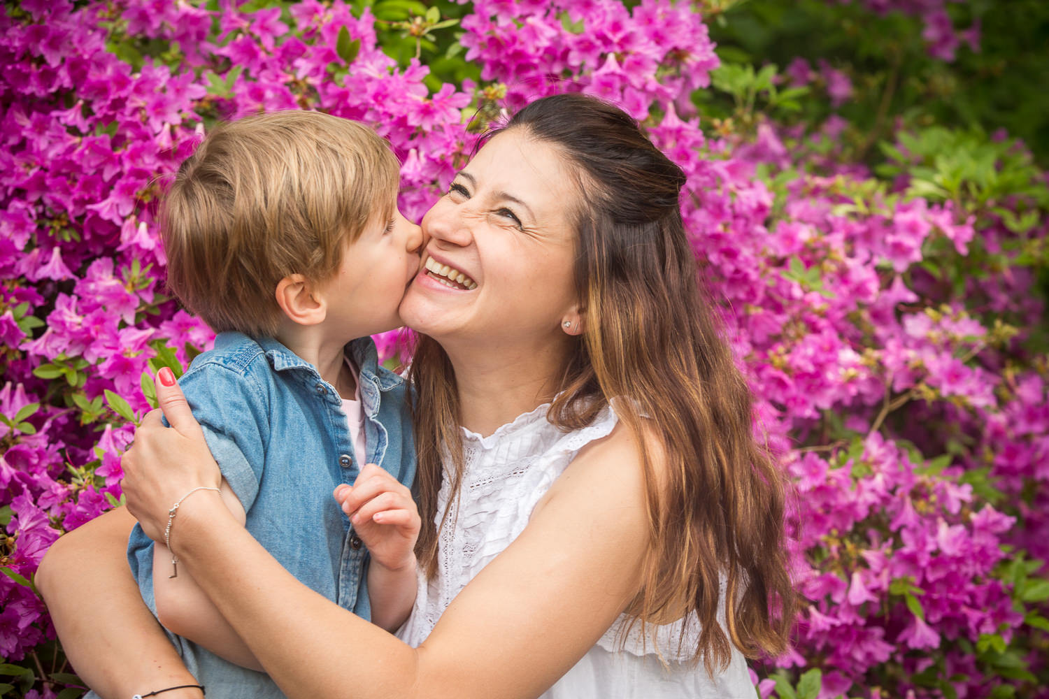mum and son have a cuddle in front of the flowers during a family photoshoot in chandlers ford