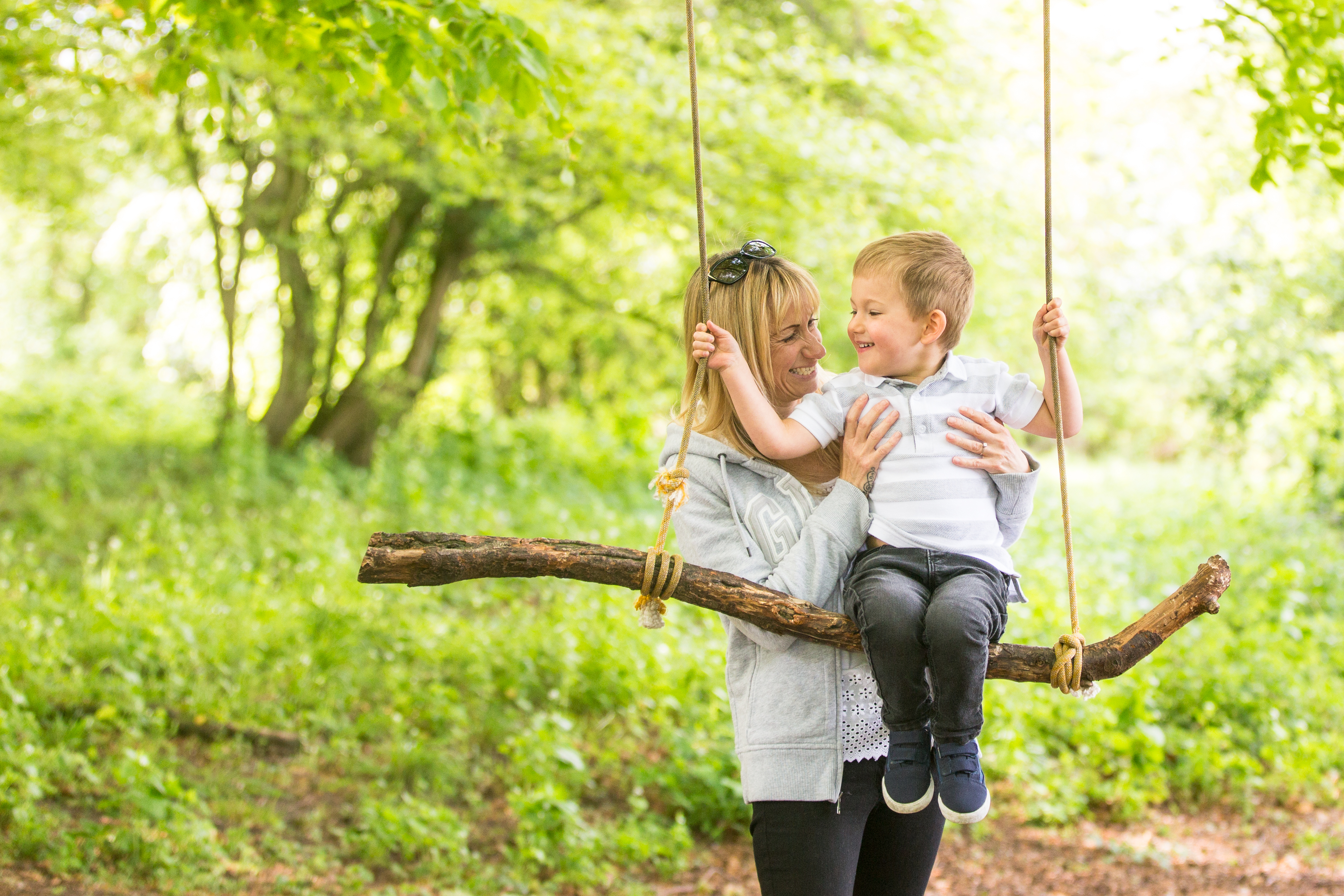 mum and son on a swing during a spring family photoshoot in chandlers ford