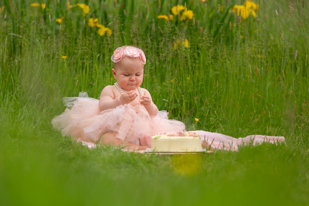 baby girl playingwith cake during outdoor cake smash in chandlers ford