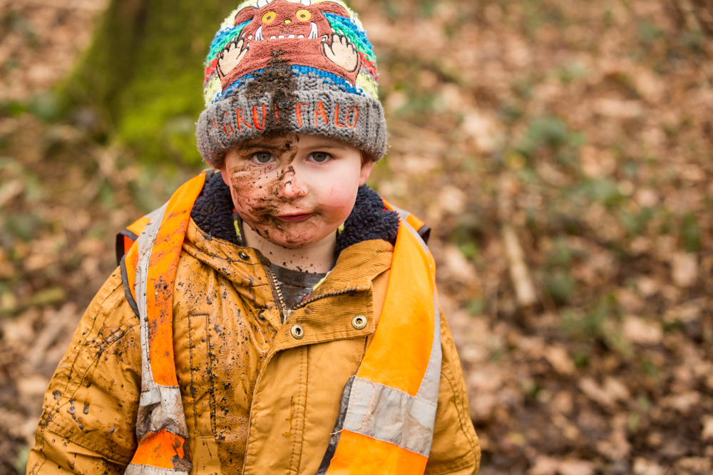 pre-school potography in chandlers ford - child with mud on his face during forest schools