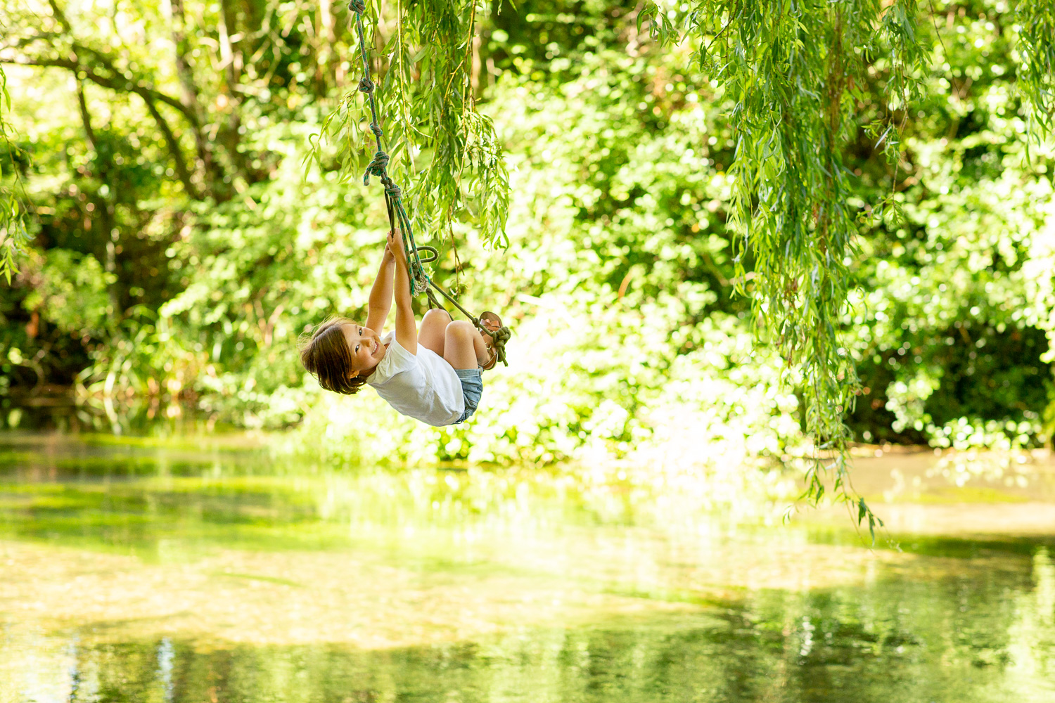 young girl swings on a rope swing during a family photoshoot in chandlers ford