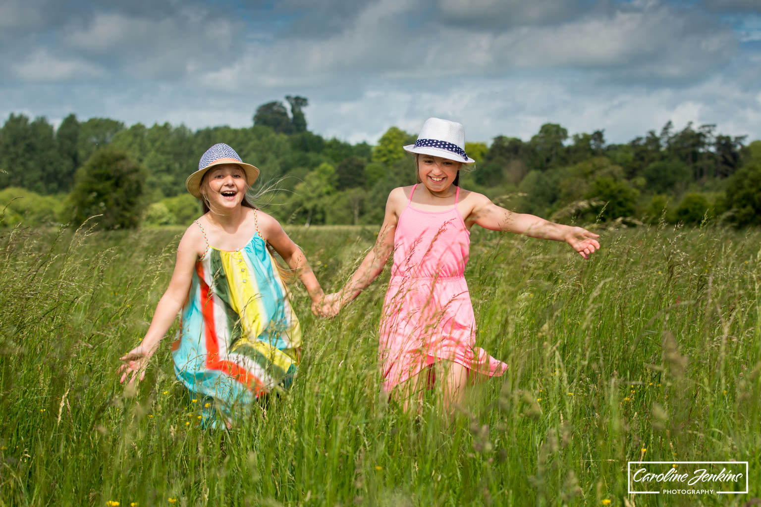 children's photography in winchester  - shot captured of two sisters running through long grass whilst holding hands and laughing