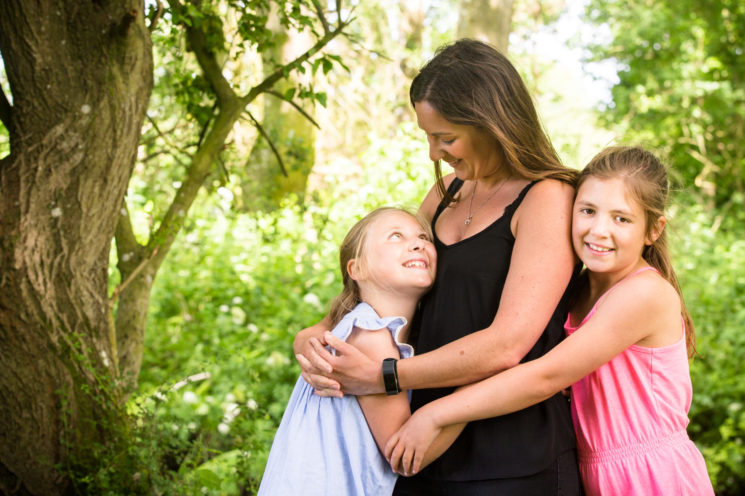 Mum and daughters cuddle during a family photoshoot in chandlers ford
