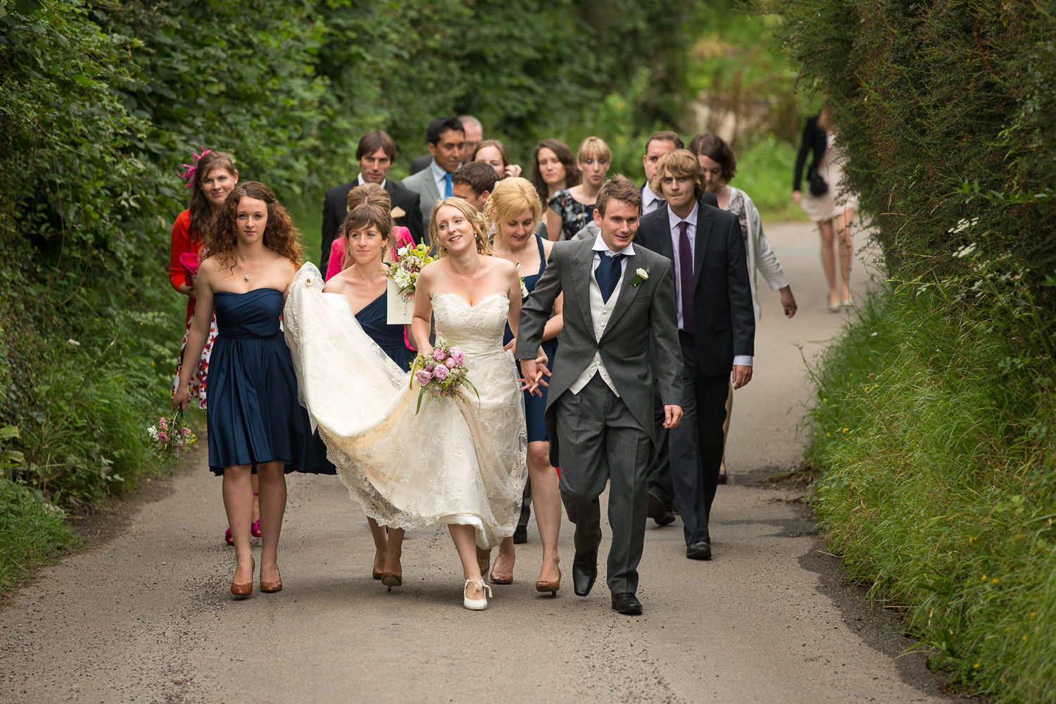 bride and groom smiling and walking down the road during their photoshoot in chandlers ford
