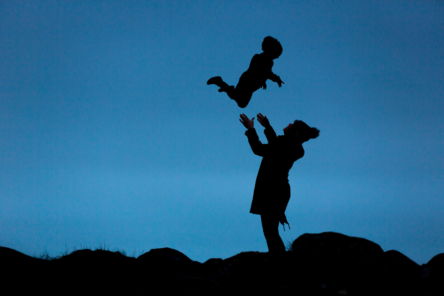silhoutte of mum throwing child in the air during family photoshoot in chandlers ford