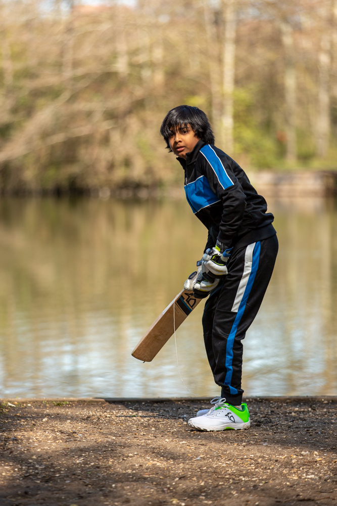 boy practises cricket during a family photoshoot at Lakeside