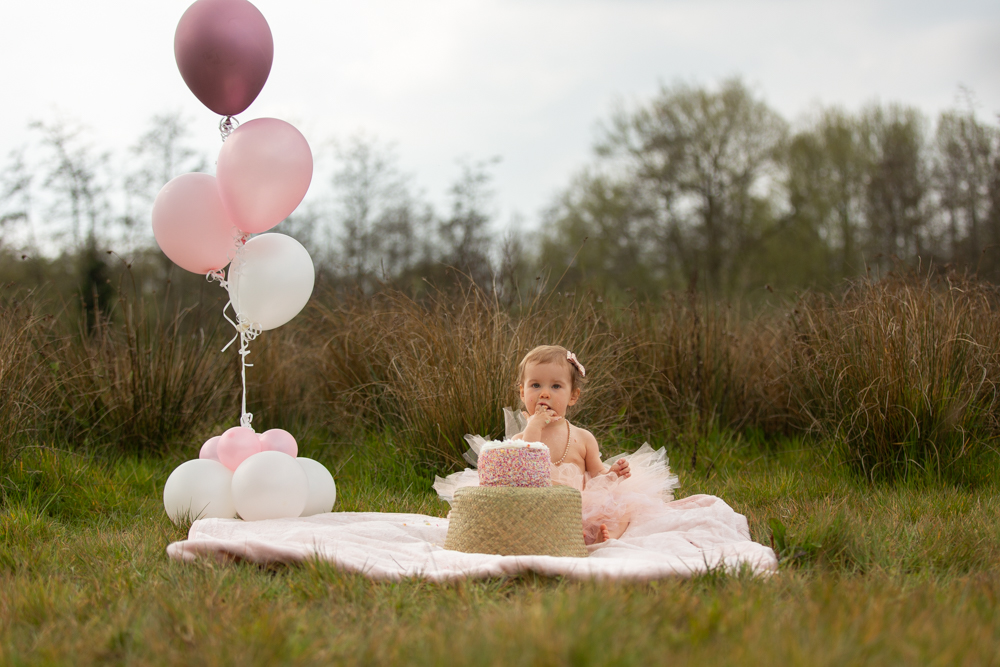 baby girl east cake outside during cake smash in chandlers ford