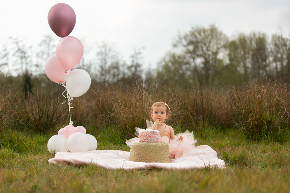 during a cake smash in Chandlers Ford a baby shoves food in her mouth