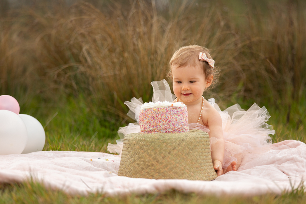 baby girl eyeing up cake during her cake smash in chandlers ford