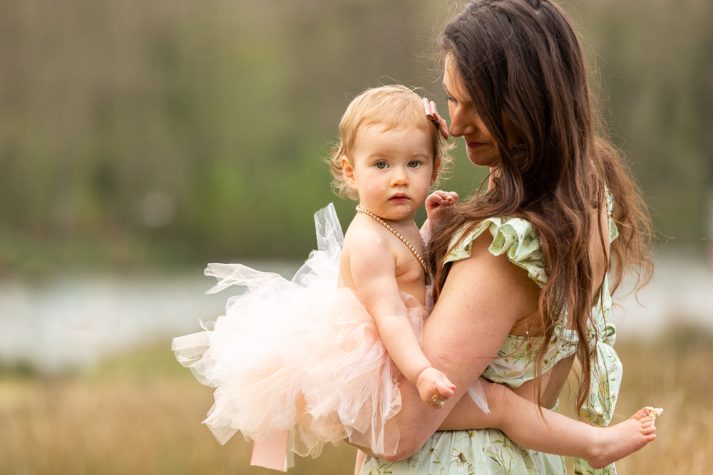 mummy and baby in a tutu during outdoor cake smash in chandlers ford