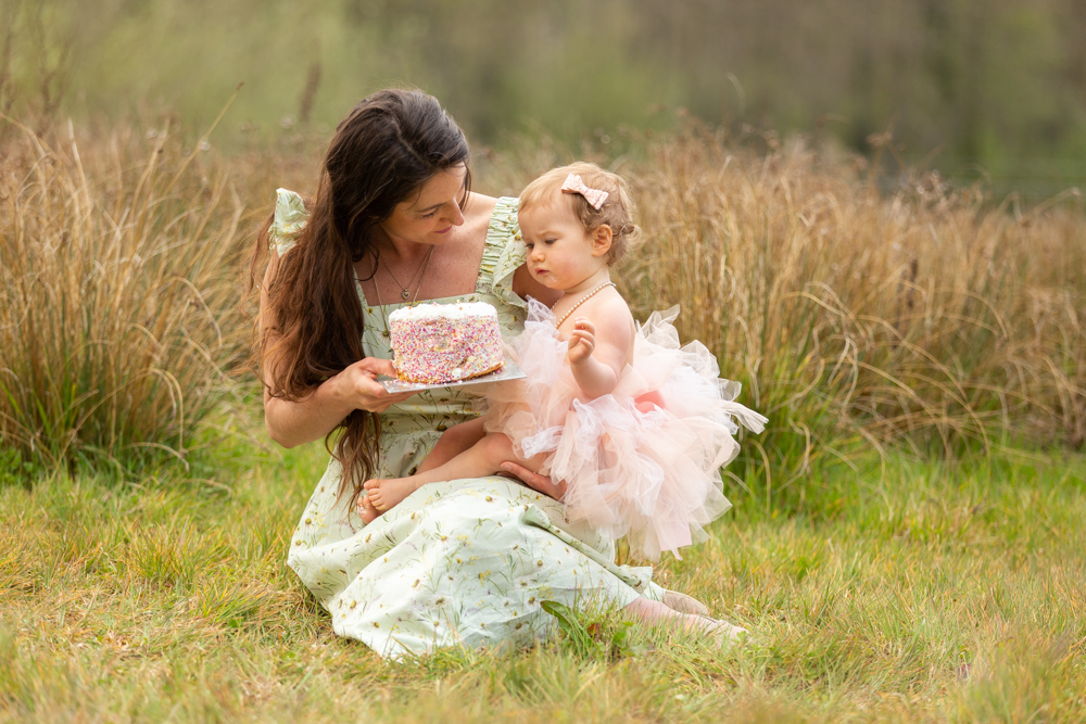 mum and baby looking at the cake during an outdoor cake smash