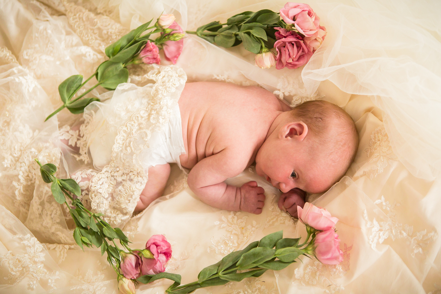 baby wrapped in mummys wedding dress during a baby photoshoot in chandlers ford