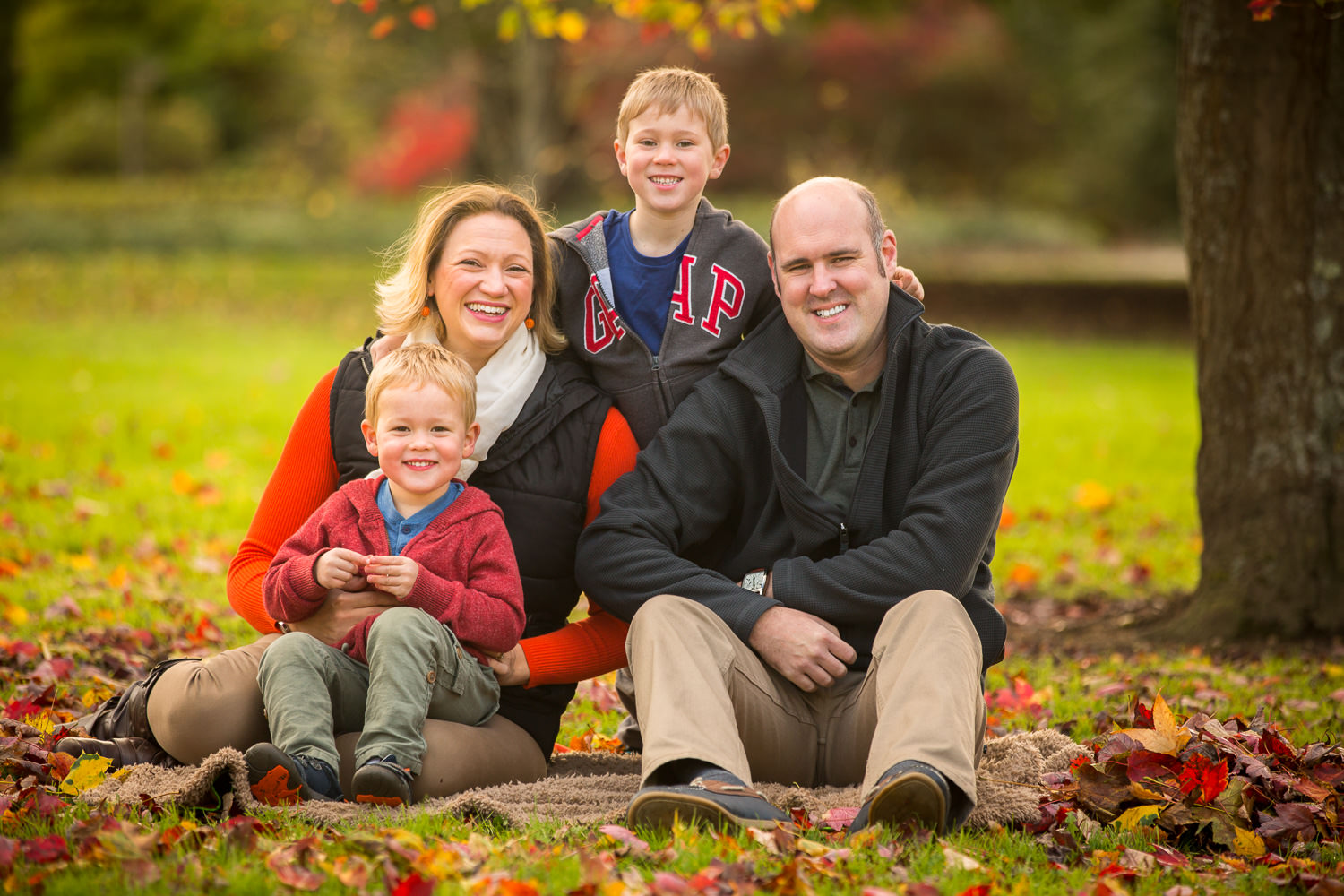 Young family pose under an Acer tree during Hilliers photoshoot