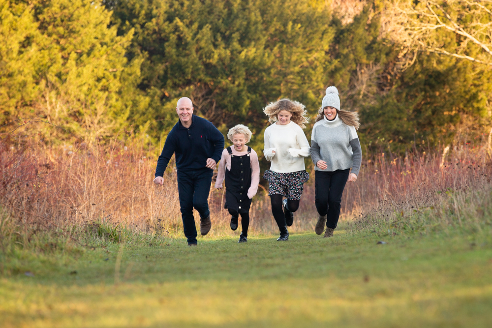 family running and laughing whilst working with photographer in Chandlers Ford