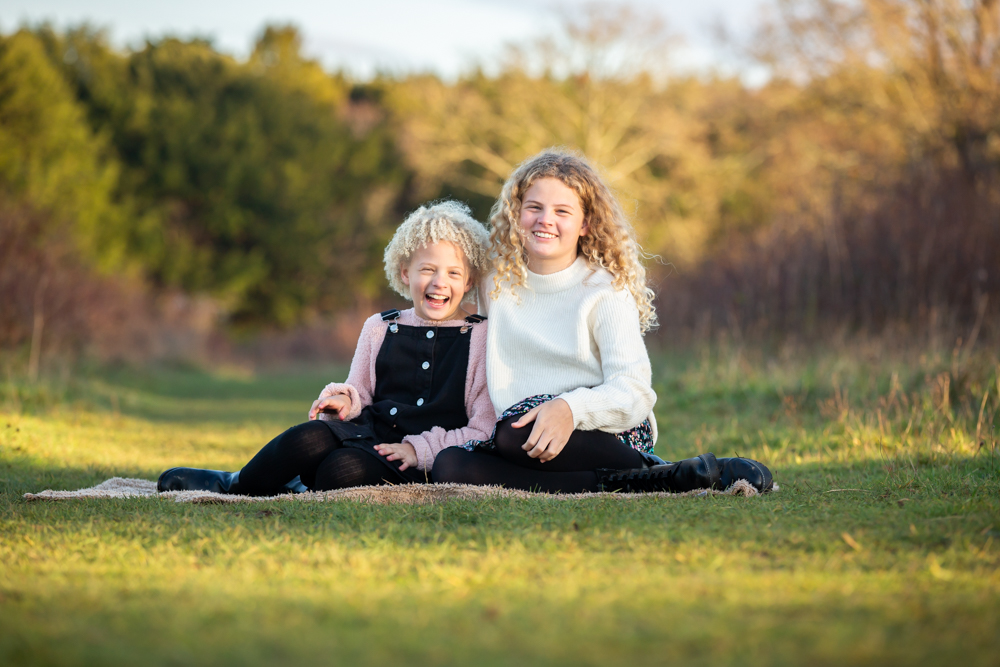 family photographer in chandlers ford - sisters on smiling on the grass