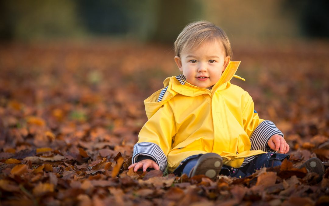 Autumn family photography in Winchester - baby sitting in autumn leaves