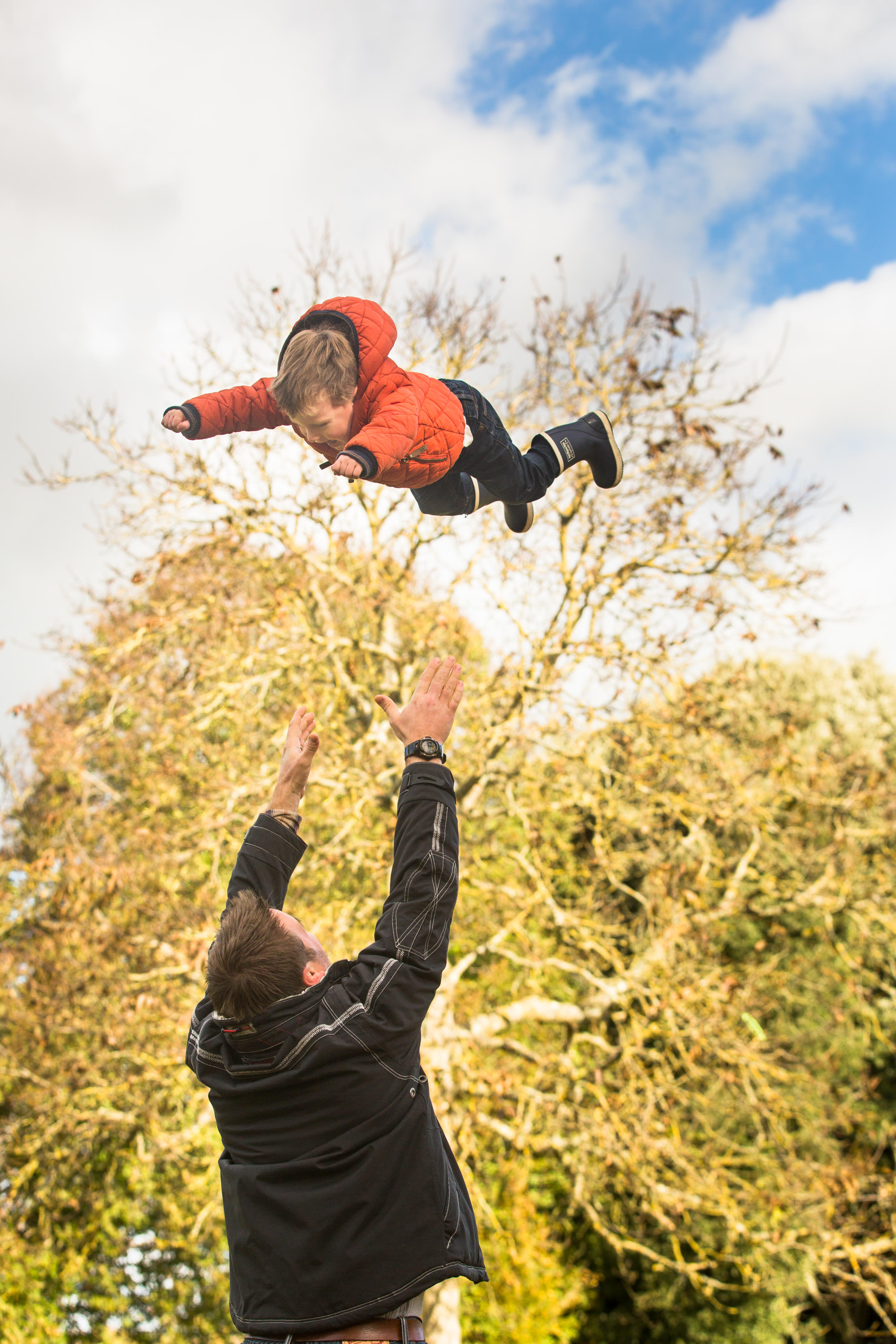 family photographer in Winchester - dad throwing toddler in the air